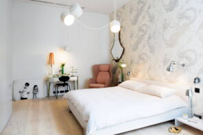 Space-Saving Solutions: Bedroom Design Ideas for Small Homes. Accent wall with pattern wallpaper and light color scheme with small working place