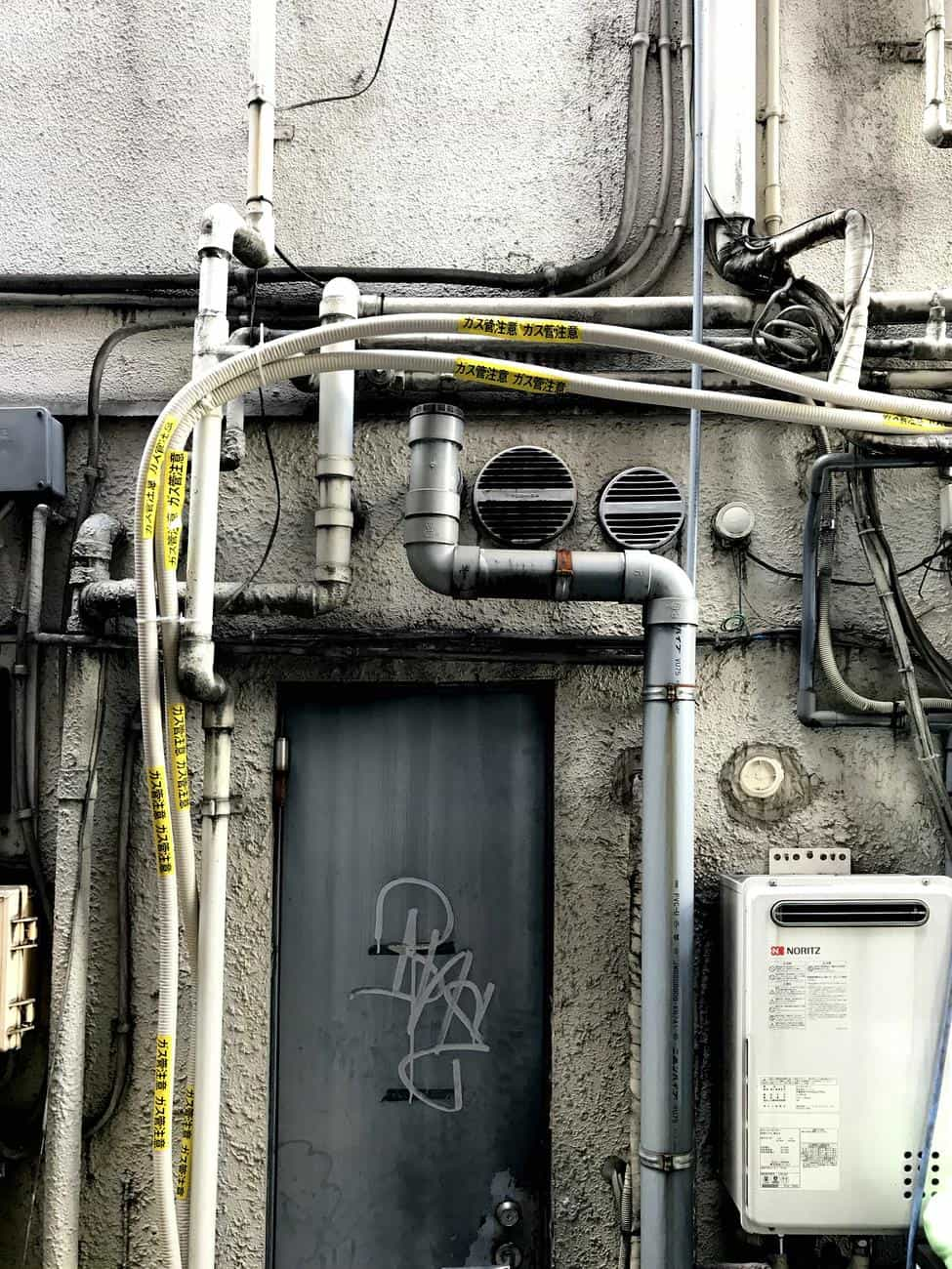 What You Need To Know Before Wiring Up Your Home. Complex wiring and pipe systems at the back of the building