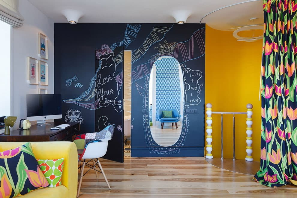 Black accent wall and yellow interior paint for creative gameroom with blackboard