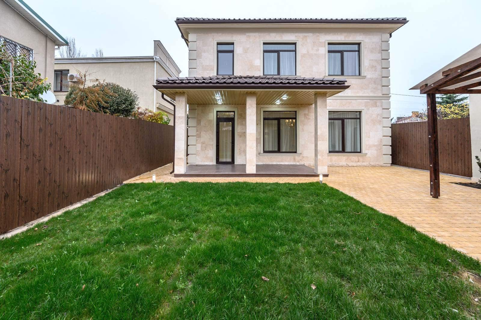 What to Consider Before Buying a New Home. Great lawn and casual facade of the light finished house with the porch in columns