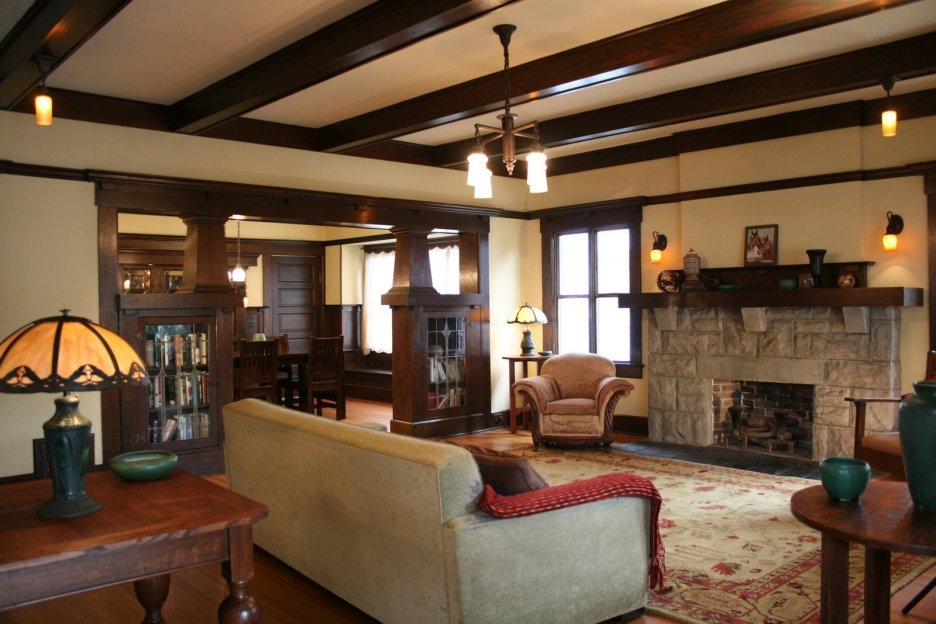 Open layout first floor of the house with exposed laquered ceiling beams and pastel colored interior with stone cladded fireplace