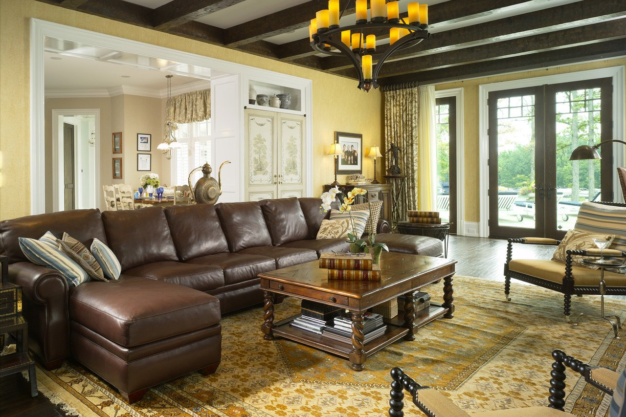Chocolate brown leather sofa and noble lacquered table along with dark wooden ceiling fir the German styled interior