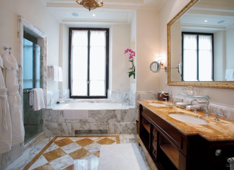 Marble sided bathtub and tiled floor in the bathroom