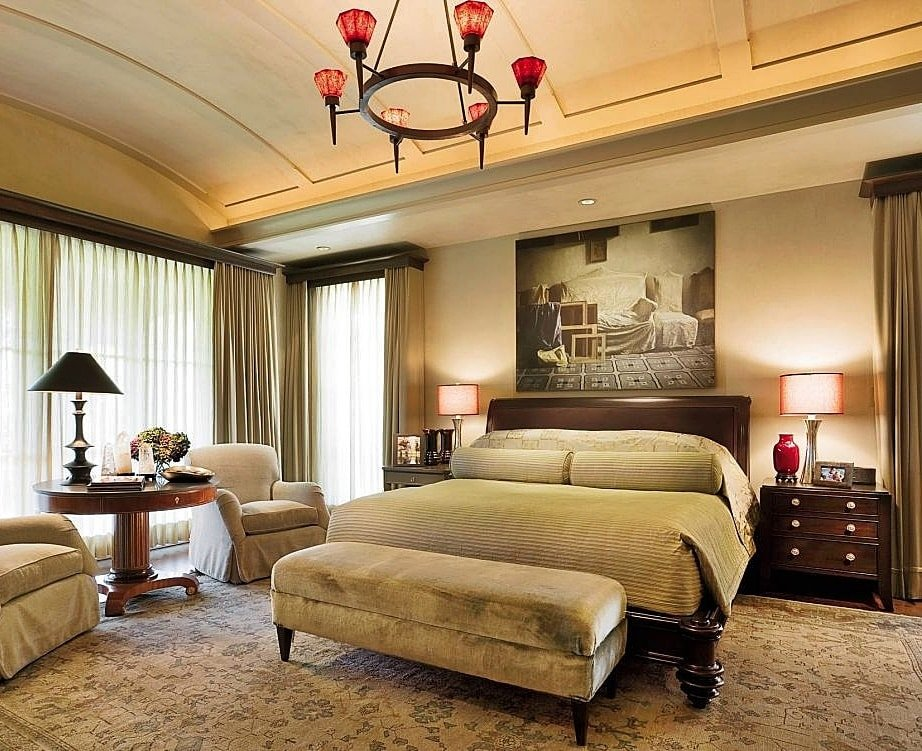 German Interior Design Style Overview and Examples. Castle chandelier with ed lampshades and LED ceiling lighting in the bedroom with kingsize bed with velour ottoman