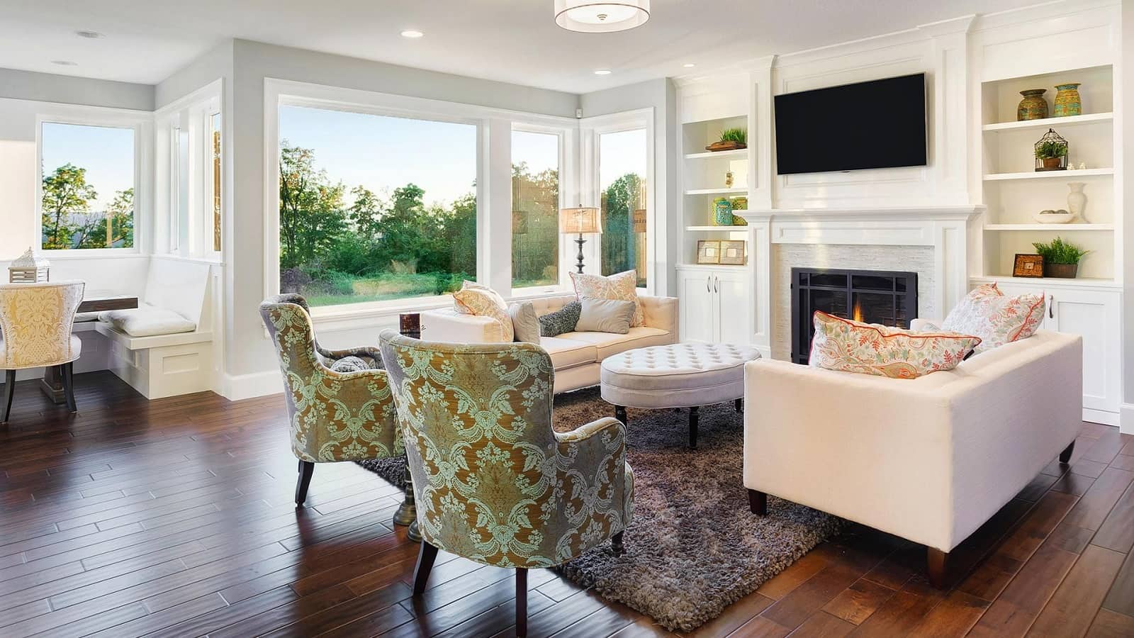 Why You Need to Stage Your Home Before Putting It up for Sale? Nice light colored open space house living room with quilted ottoman and fireplace