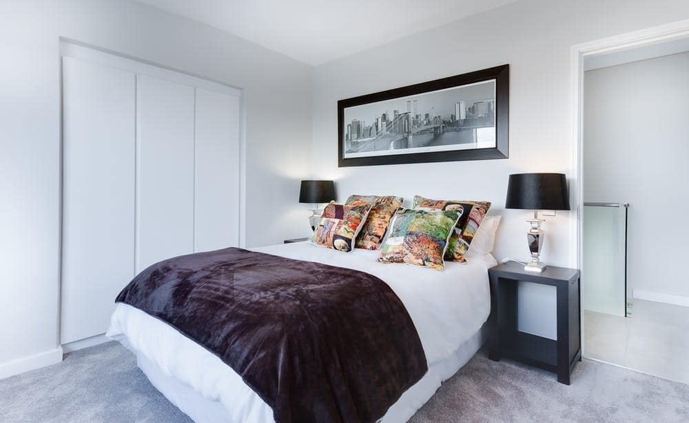 Protect Your Health with Organic Bedding and Pillows. Casual neat bedroom interior with panoramic picture at the headboard