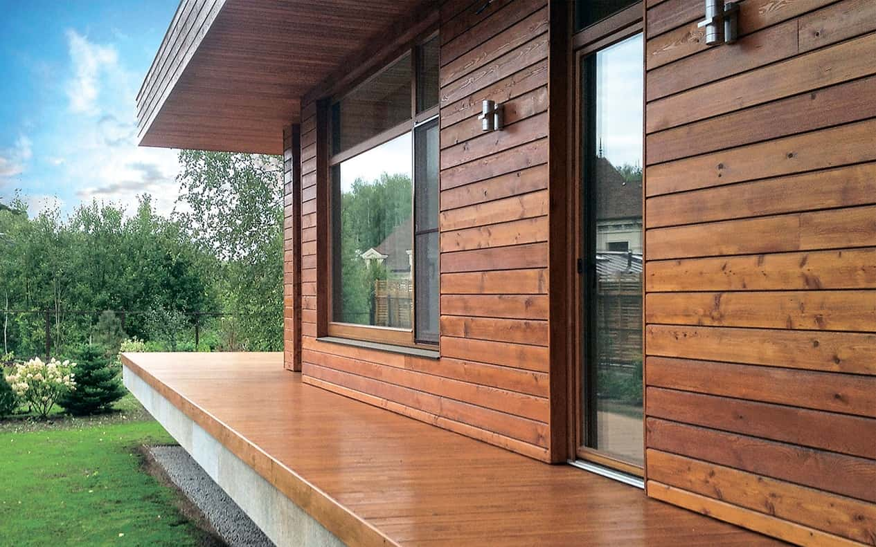 5 Tips On Choosing The Right Cladding For Your House. Lacquered wooden deck and house facade at the suburban area