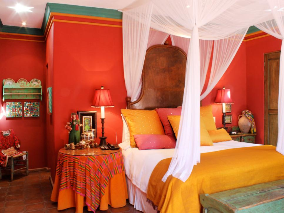 Spanish Interior Design Style Overview. White tulled canopy, red colored walls and ethnic motif if bedroom decoration
