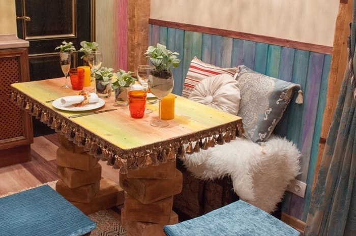 Nice dining corner decorated with colorful wainscoting and abundance of textile and fur