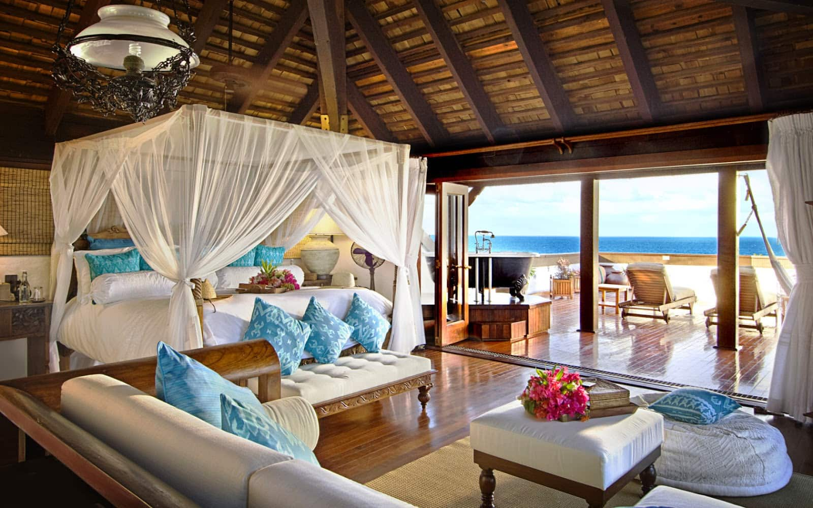 Great open space design of the oceanside bungalow with white canopy bed in the center