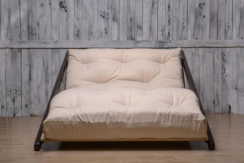 Differences Explained: The Ultimate Futon vs. Bed Comparison. Sofa on simple wooden frame with thick futon mattress