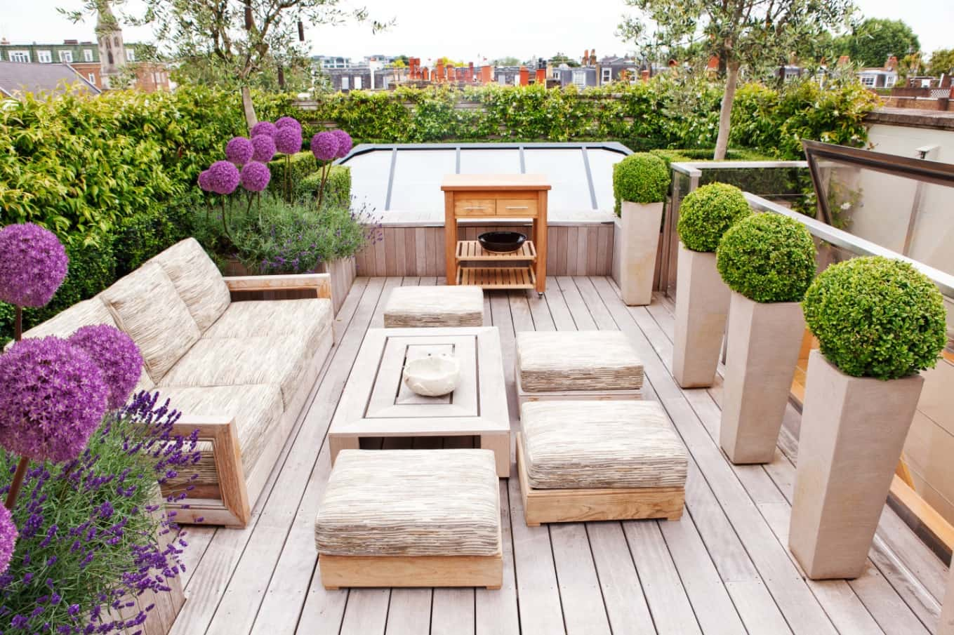 Top Tips for Designing Your Patio. Modern design with wooden coffee table and bonsai flowers in high concrete vases
