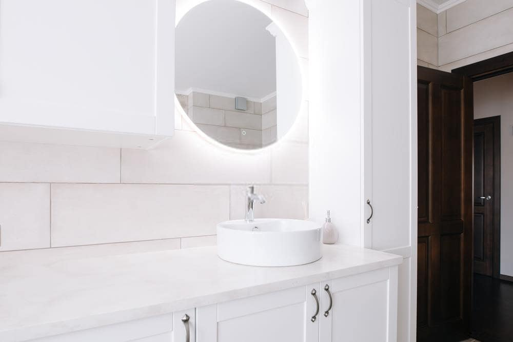 Neat white bathroom with round mirror with LED backlight