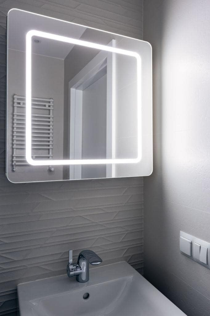 Heated towel rail and the backlighted mirror for small bathroom