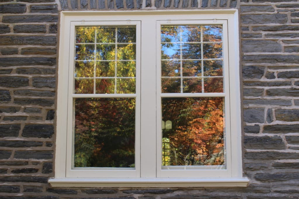Safe and Sound: How to Protect Your Home During Storm Season. Wooden storm windows for classic facaded house