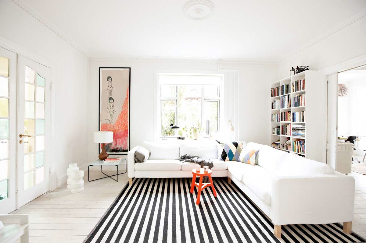 Zebra rug and orange stool with corner sofa in the light colored library