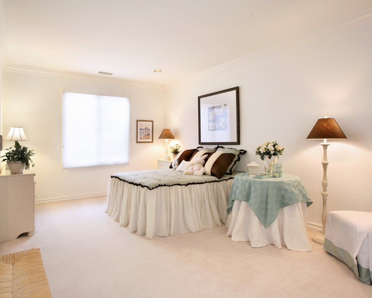 White boxed bedroom with black framed picture at the headboard