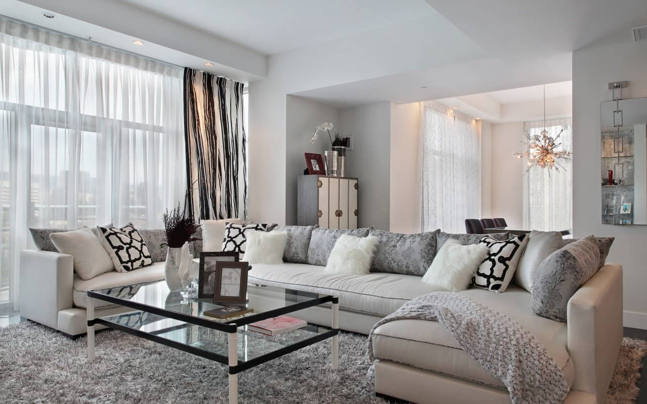 Gray and pastel color scheme for large airy designed living room with tulle and draperies as well as gray fluffy rug