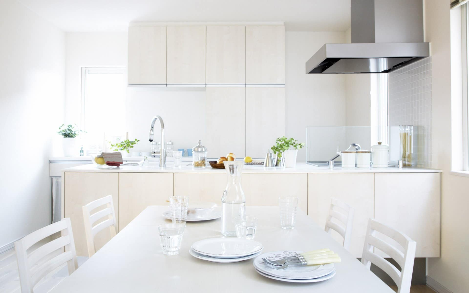 Pastel colored kitchen with minimalistic furniture set and white table