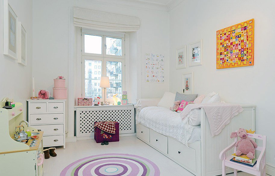 Warm atmosphere in the light pastel colored children's room with accent in the form of orange picture