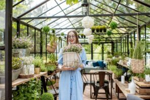 6 Benefits Of Having A Small Greenhouse In Your Home. The girl in the eco space with the bouquet of flowers in the pot
