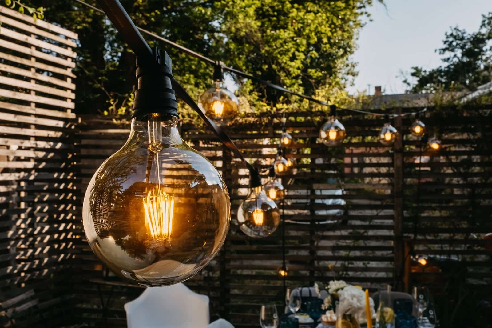 15 Outside Lighting Ideas To Brighten Your Home. Black electric cord with incadescent light bulbs in steampunk style over the patio zone at the backyard