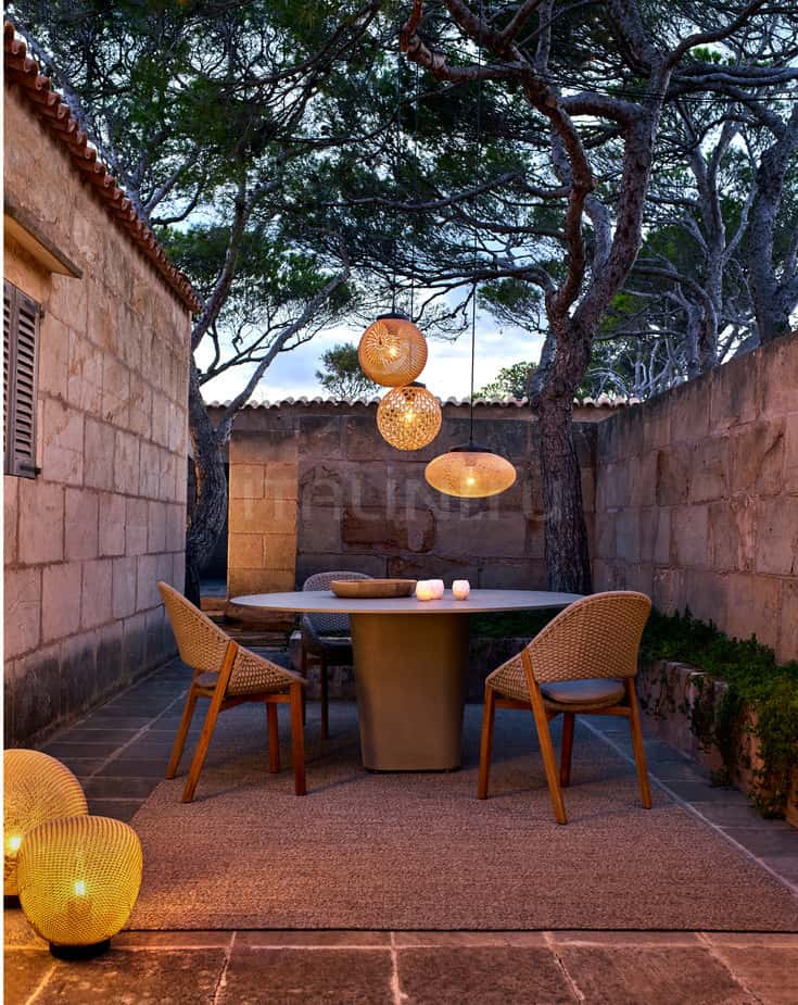 Nice backyard patio area with pendant lighting over the round table and rattan furniture