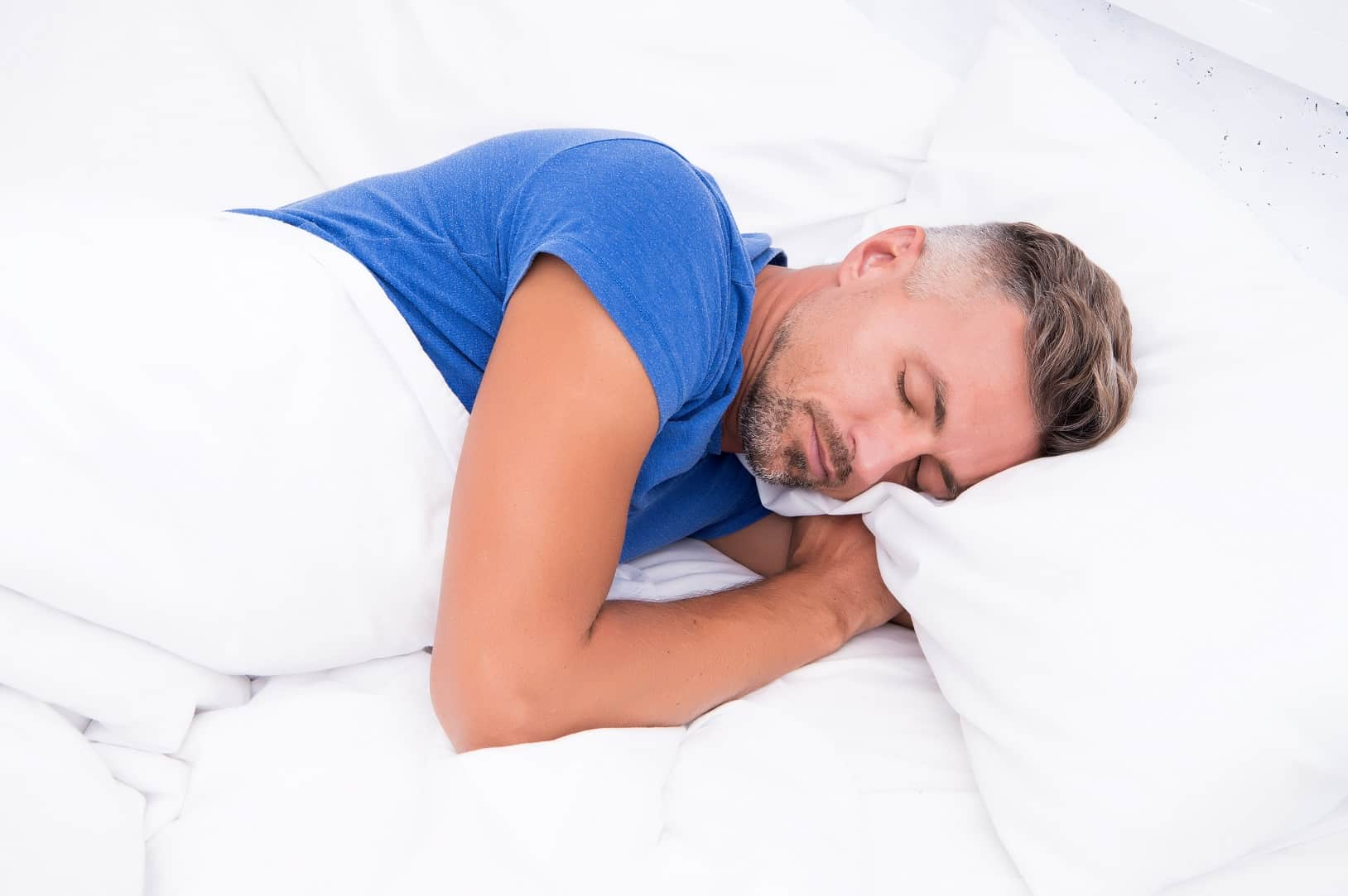 Trouble Sleeping? Here's How To Promote Better Sleep. Sleeping man in the blue shirt
