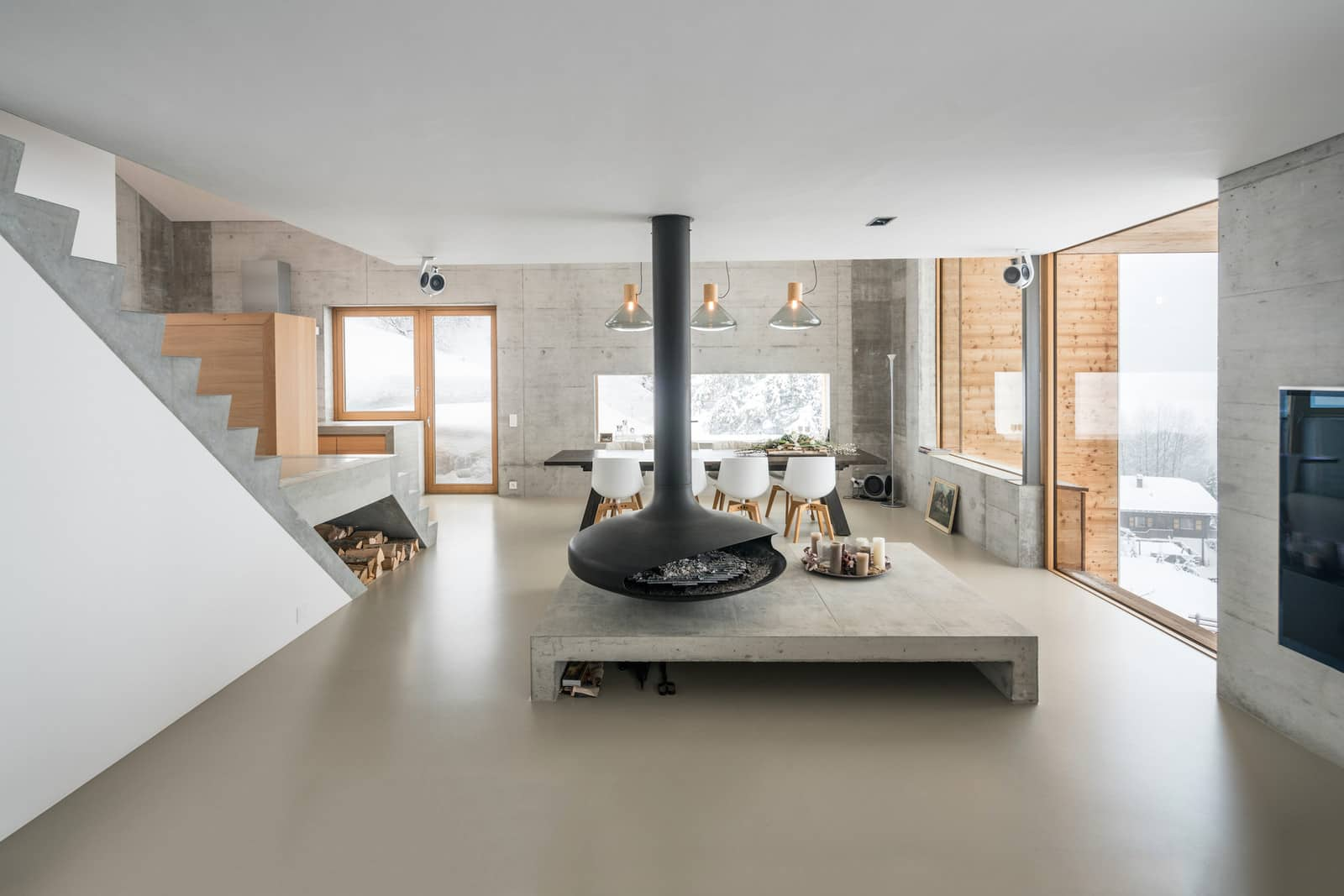 7 Things to Do to Avoid Home Buying Regrets. Great chalet house interior with central grandeur fireplace and hi-tech concrete firewood storage