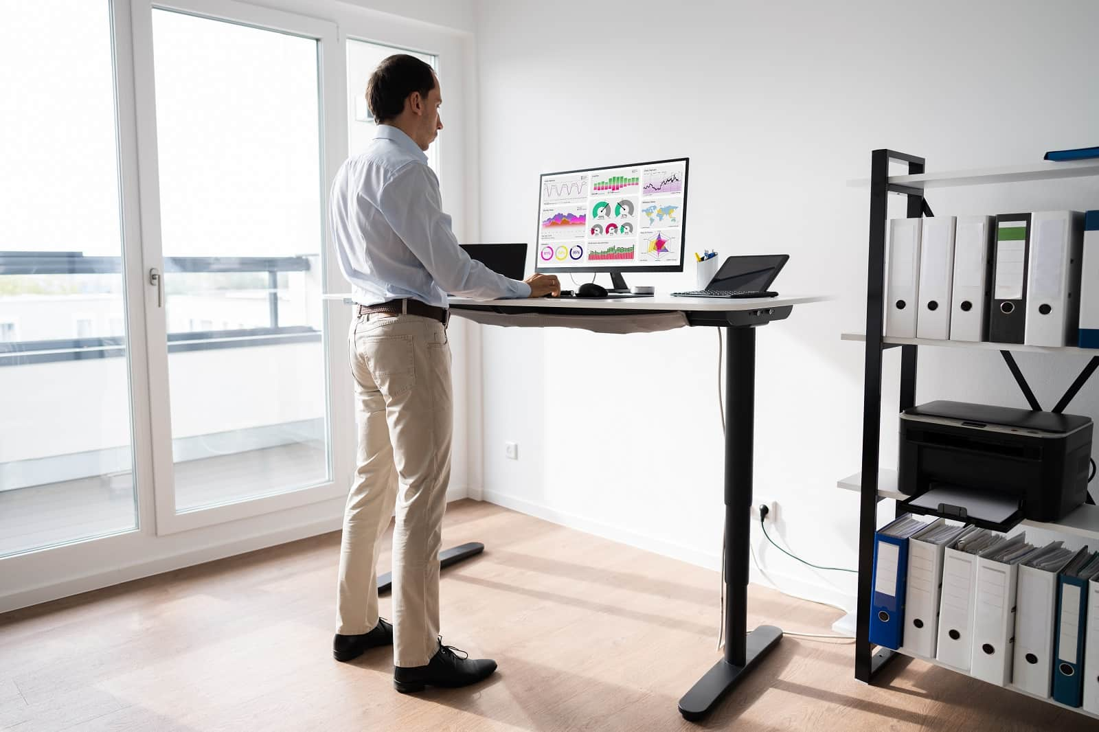 5 Factors To Consider When Choosing A Standing Desk. Working in the minimalistic home office with white walls and light wooden floor