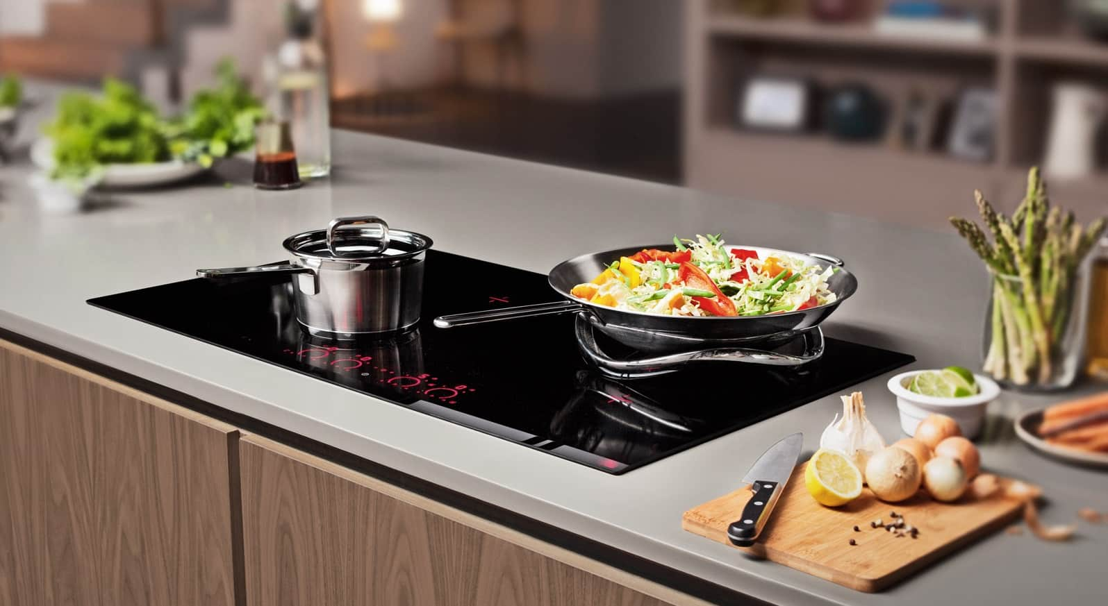 How to Remodel Your Kitchen In a Single Weekend. Frying pan with a salad on a modern built-in hob
