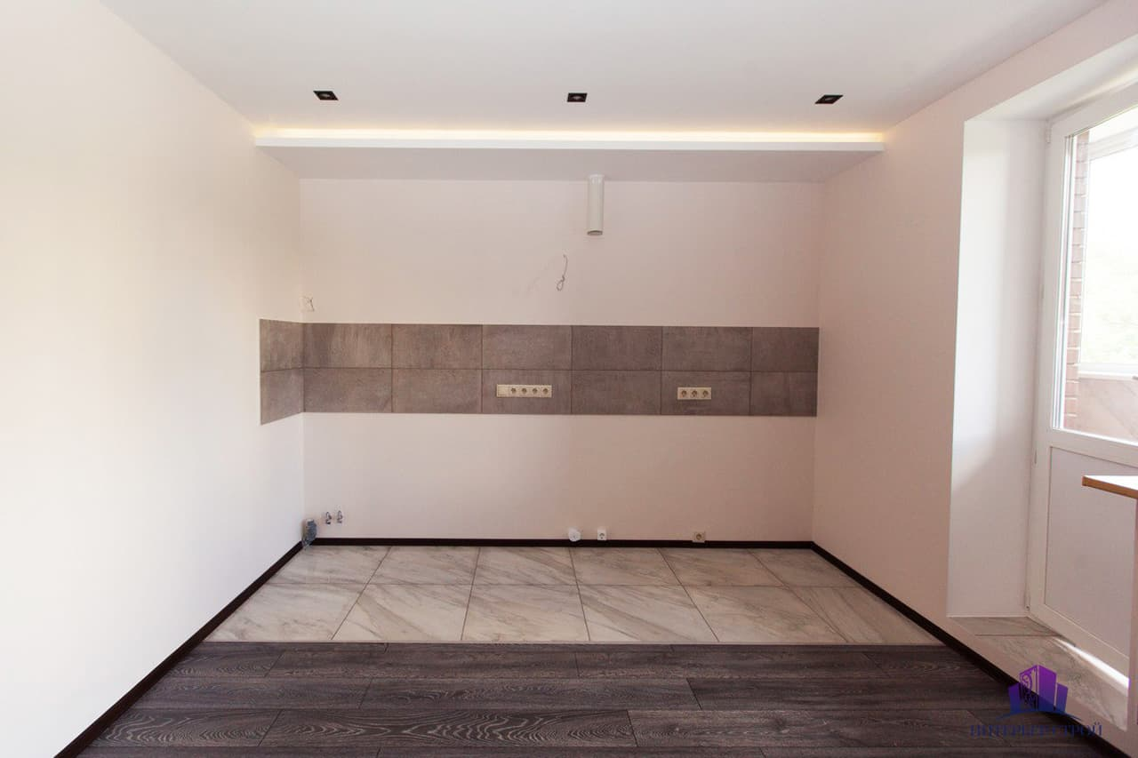 How to Remodel Your Kitchen In a Single Weekend. Staged empty kitchen with no furniture and just a floor and backsplash finished