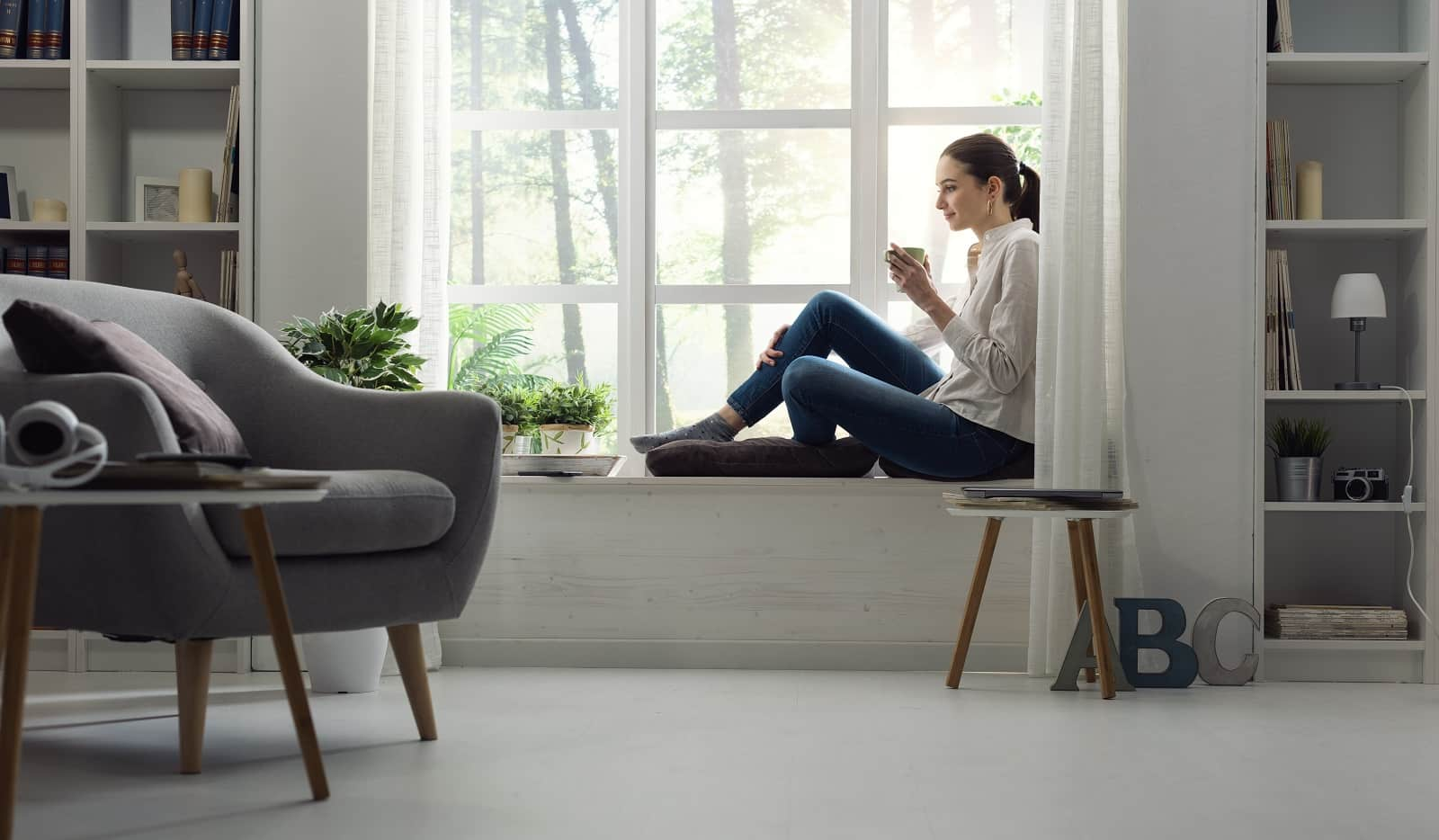15 Simple Changes That Can Make Your Living Room Much Cozier. White colored Scandi styled living with large sash window and gray furniture in wooden legs