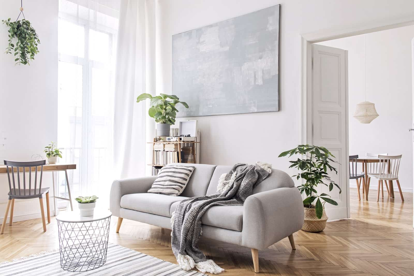 15 Simple Changes That Can Make Your Living Room Much Cozier. Minimalistic design with gray sofa and plants along with black chalkboard at the wall