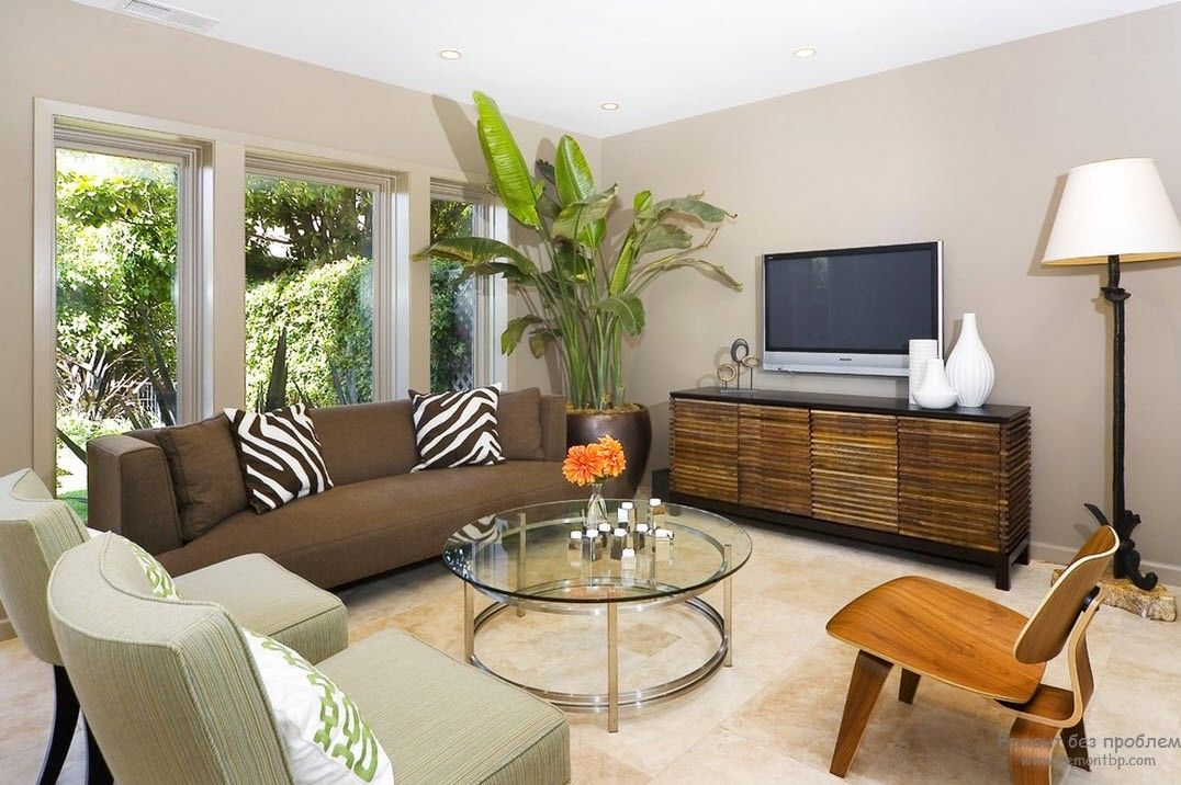 Round glass table and brown furniture for a pastel colored living
