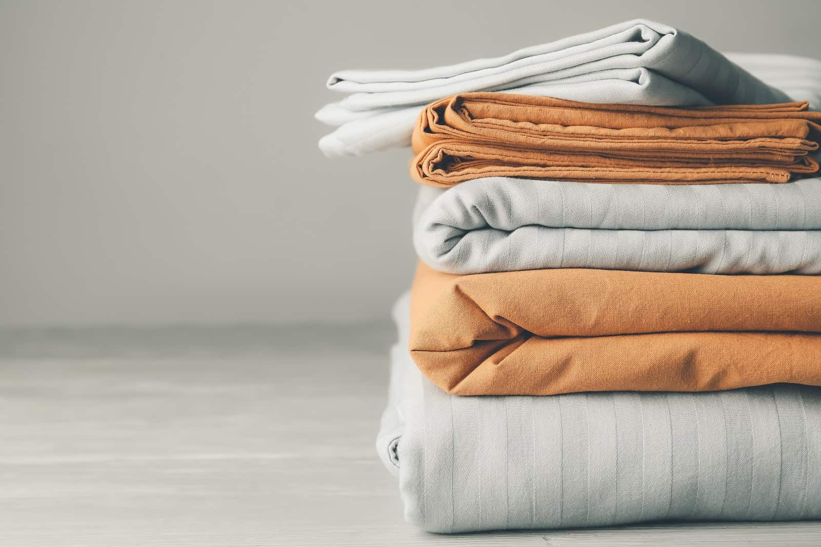 How To Find The Perfect Bedding For Your Room. Furled bedsheets of gray and orange colors