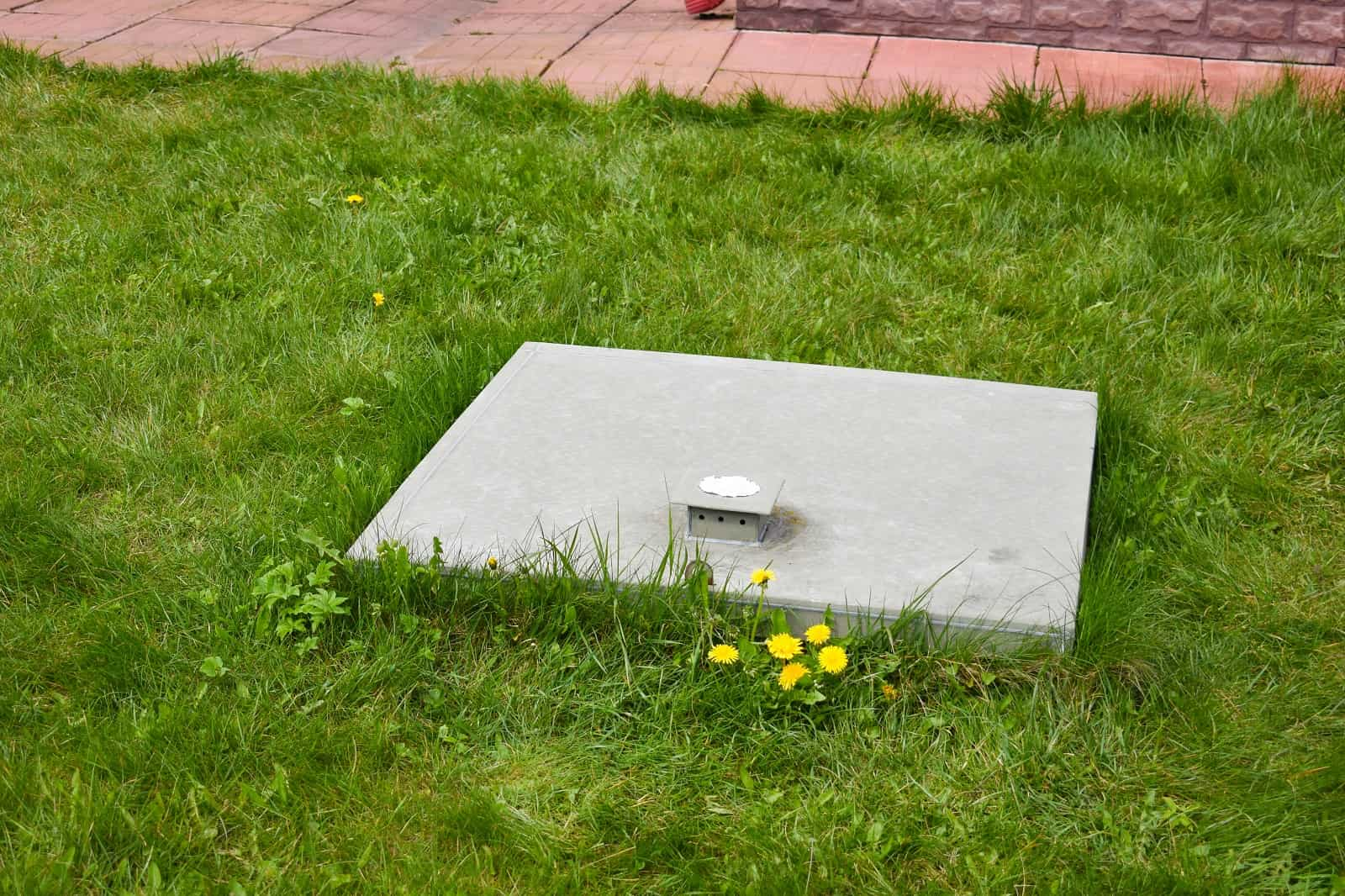 How To Find The Best Plumber For Septic Tank Repair And Installation. Septic tank lid in the grass