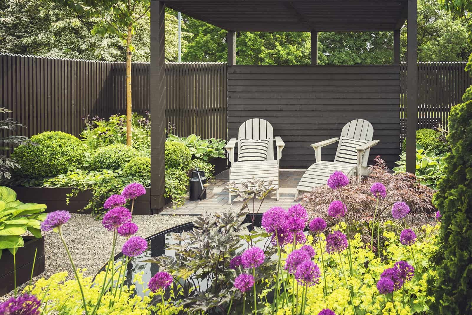 5 Benefits Of Reclining Garden Furniture. Backyard patio zone surrounded with blossoming plants