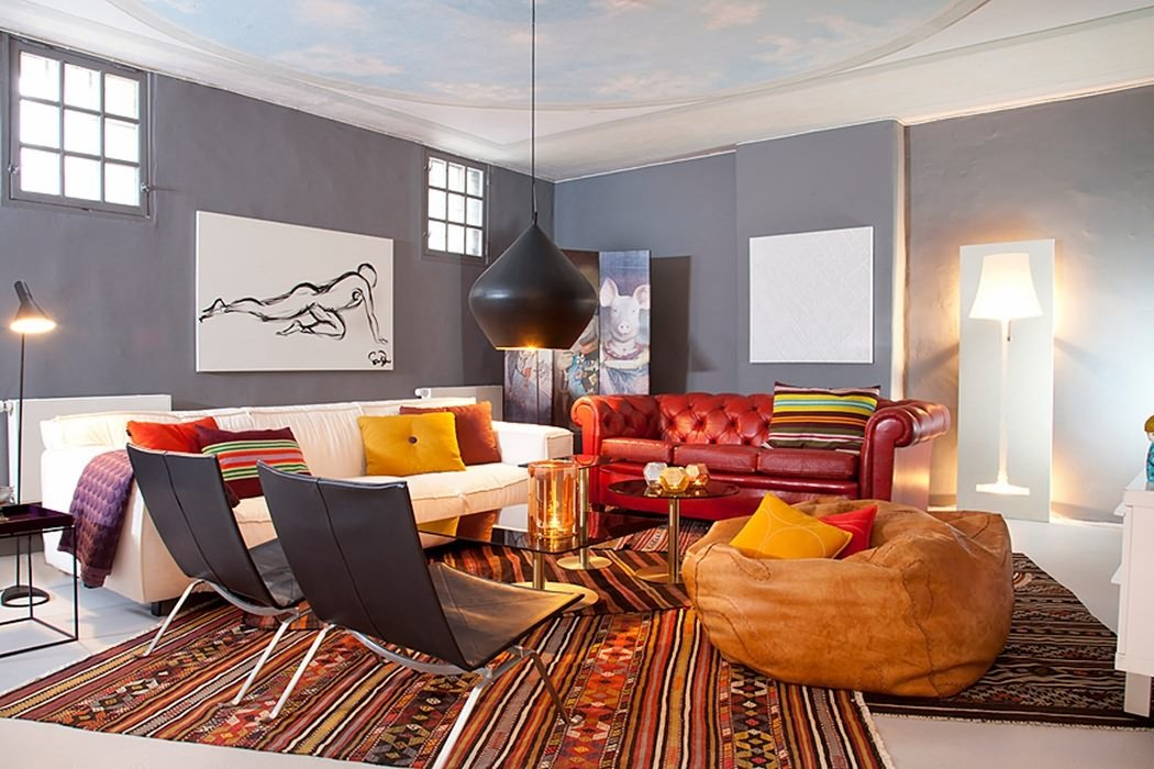 Urban Style Interior Design: The Essence of Big City at Home. Colorful interior with Arabian rug and red quilted sofa