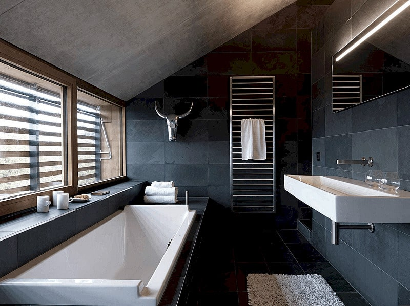 Black accent wall and sloped ceiling to emphasize white tub and vanity