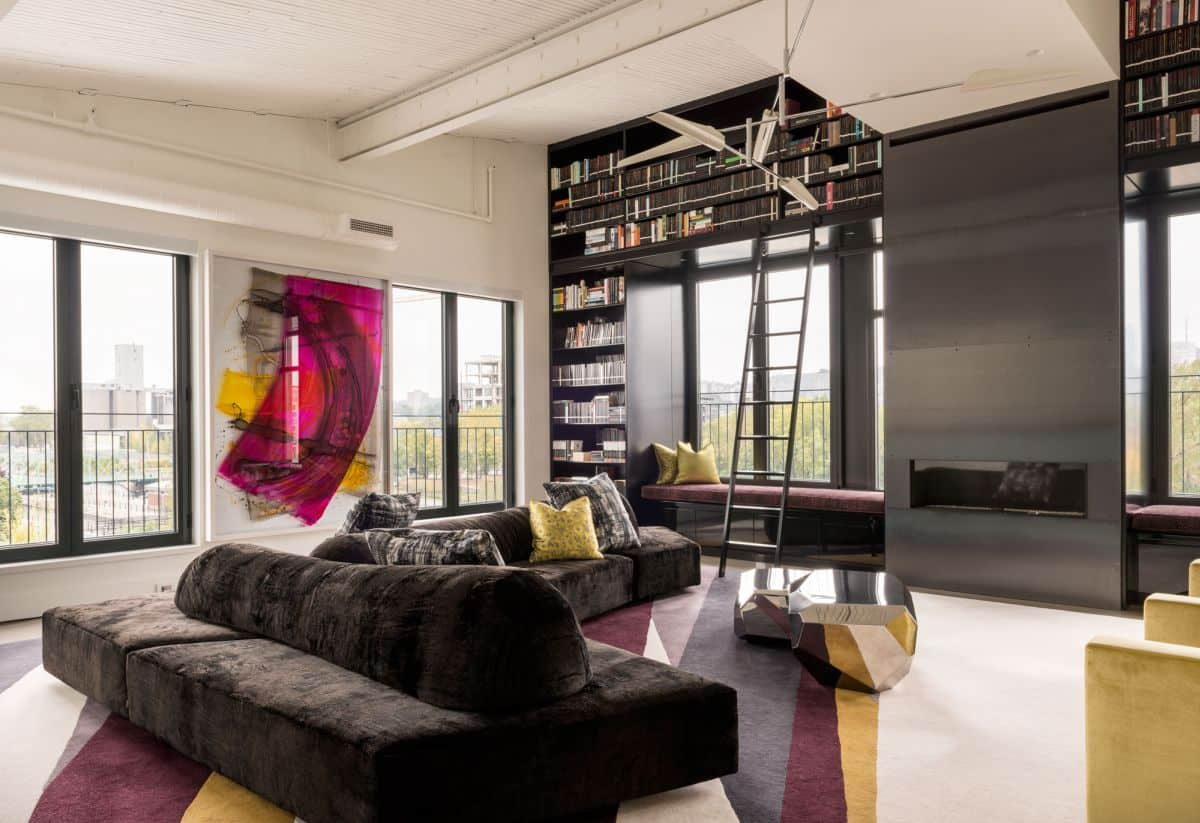 Unusual open layout studio apartment with top located library double-sided sofa and pop art color palette
