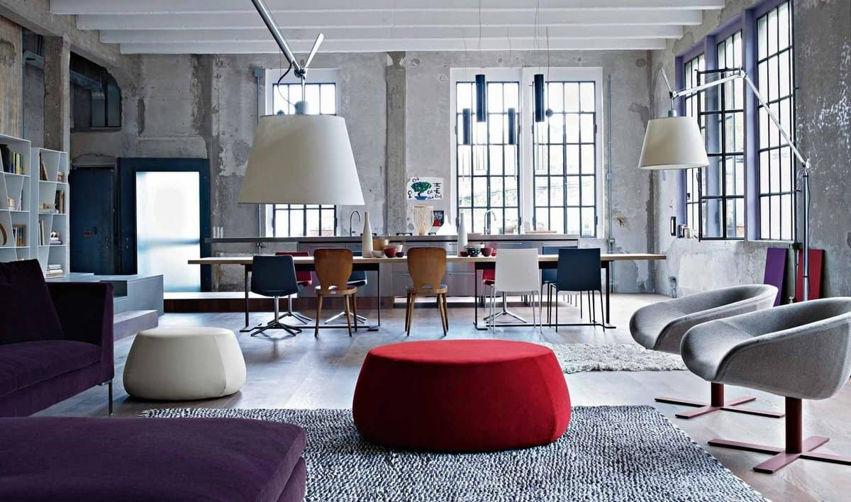 Accentual red ottoman in the center of open layour studio with fluffy rug and large sash windows