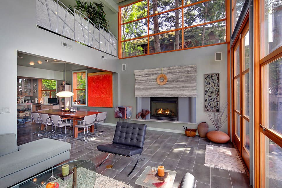 Urban styled house interior with double ceiling, large fireplace and domination of gray