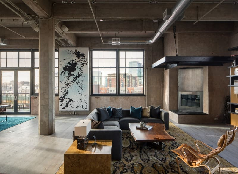 Successful interior design in the former industrial area reworked into modern urban styled studio with pieces of art, sitting zone and exposed columns