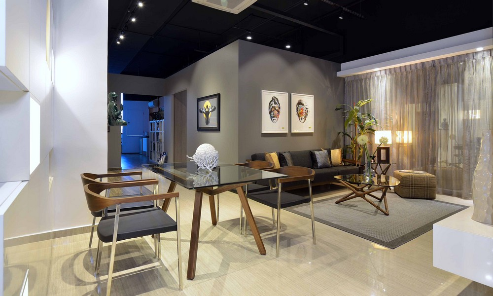 Gray walls, dark illuminated ceilnig, glass topped table and light colored floor for open layout urban apartment