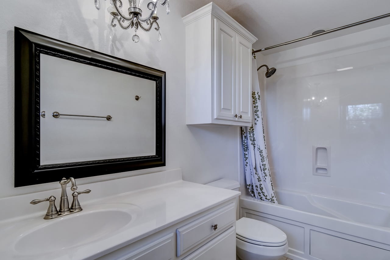 5 Bathroom Remodeling Trends to Consider. Classic vanity and hanging cabinet in Art Deco styled space with chandelier white tiling