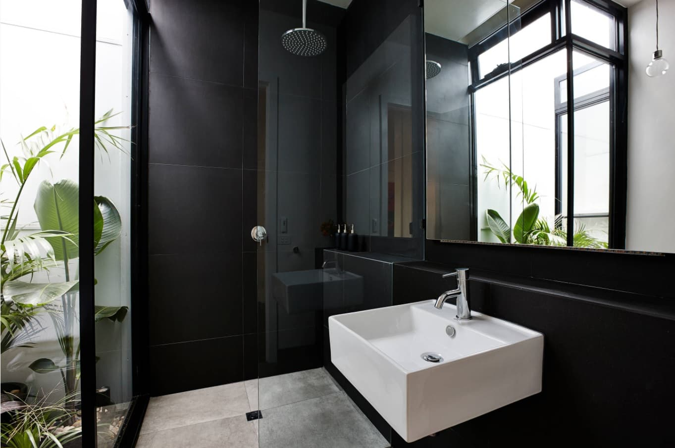From Basic to Fancy: How to Upgrade Your Bathroom with New Trending Décor Ideas. Fully black walls and white urban sink in the natural lit area