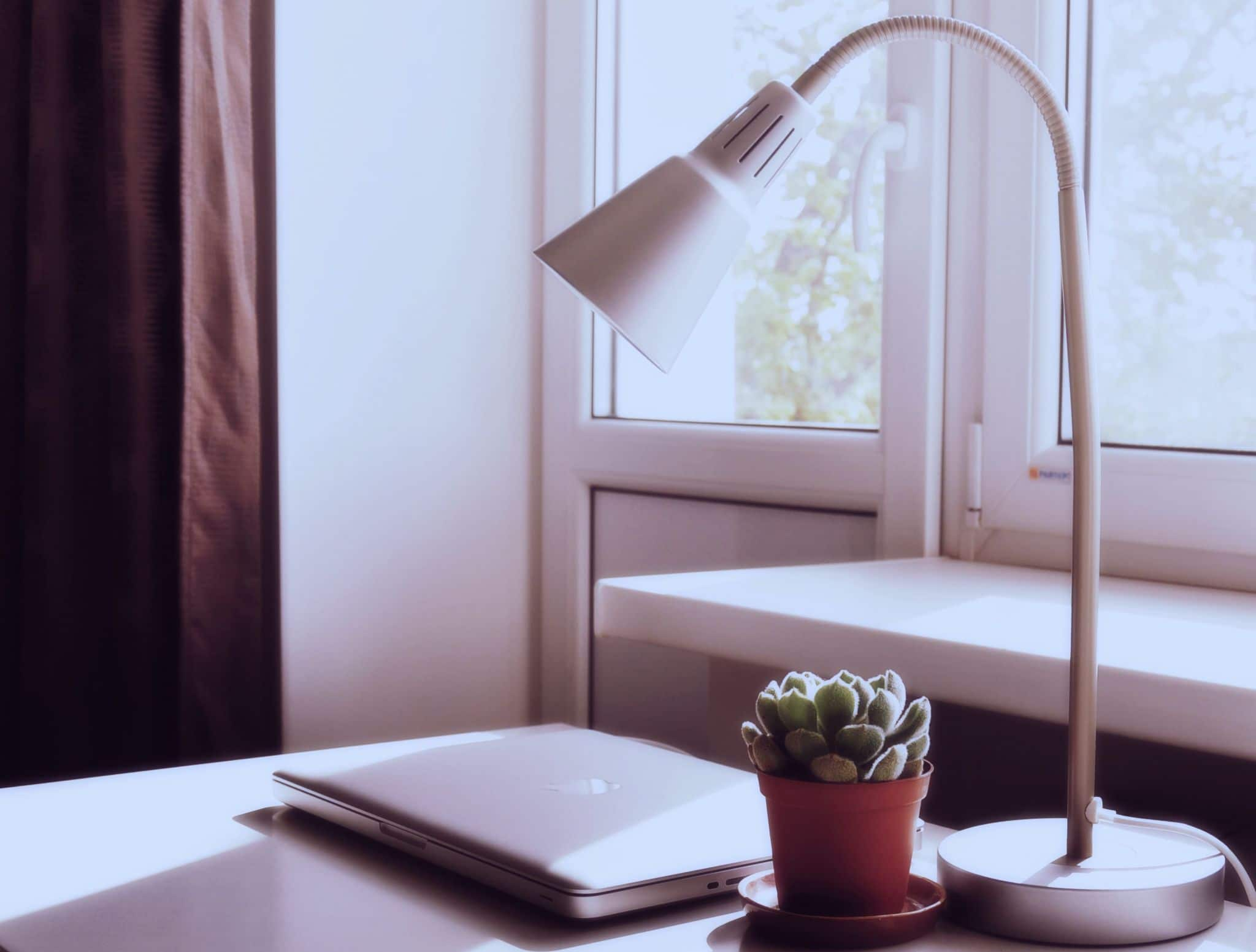 How to Improve Your Home Office Lighting. Desktop with adjustable lamp in the casual minimalistic interior