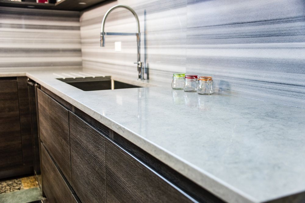 Laminate vs. Quartz Countertops: What is the Price Difference. Gray countertop and splashback for modern-style minimalistic kitchen