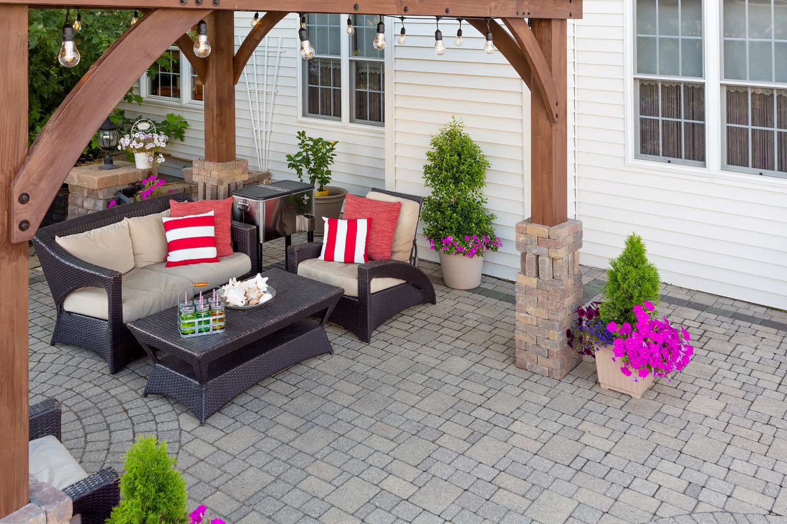 9 Ways To Liven Up Your Patio. Stone paved patio under the wooden awning with rattan furniture near the white sided house